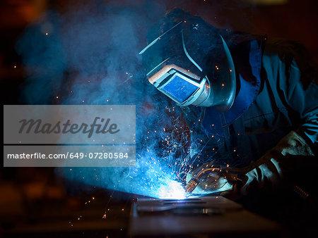 Welder using oxyacetylene torch in factory