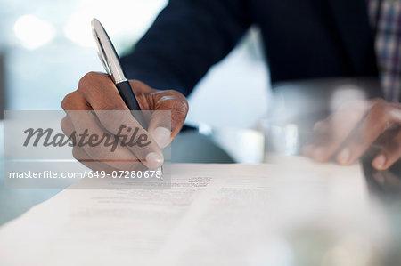 Cropped image of businessman signing paperwork