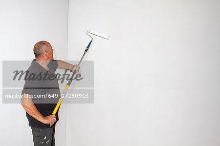 Studio shot of senior roller painting room walls