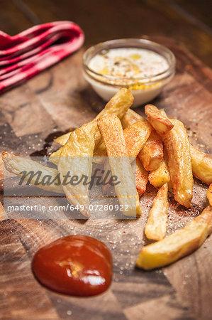 Still life of potato fries, ketchup and dip