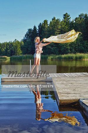 Young woman shaking blanket on pier, Gavle, Sweden