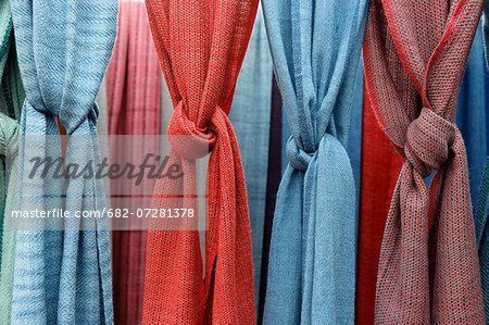 India, New Delhi. Display of hand woven shawls at Dilli Haat crafts bazaar.