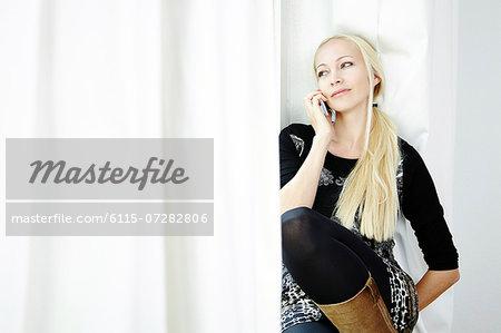 Blond woman using phone, Munich, Bavaria, Germany