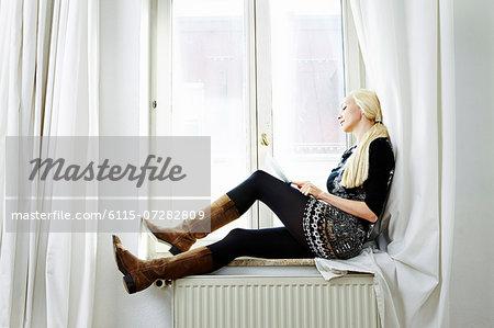 Blond woman sits at window, using computer, Munich, Bavaria, Germany
