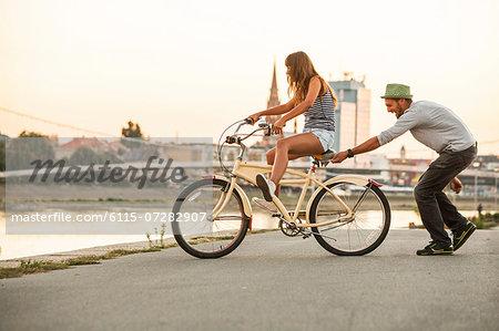 Young couple with bicycle, having fun, Osijek, Croatia