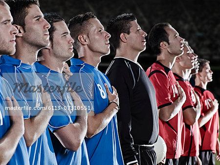 Soccer teams listening to anthem on field