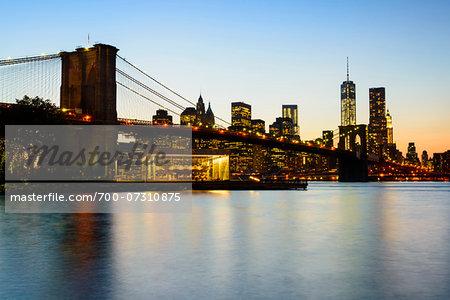 Downtown Manhattan skyline with Brooklyn Bridge and Freedom Tower illuminated at night, Manhattan, New York City, New York, USA