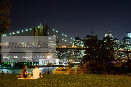 People sitting on grass in park, Downtown Manhattan skyline with Brooklyn Bridge illuminated at night, Manhattan, New York City, New York, USA