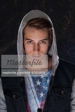 Portrait of teenage boy wearing hoodie and looking at camera, studio shot