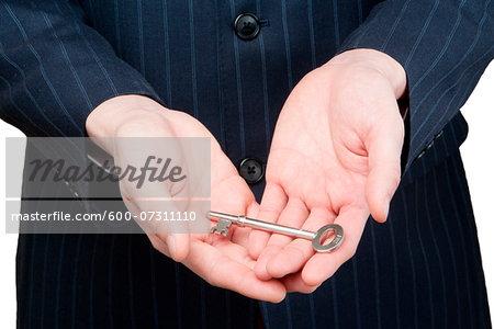 Close-up of man's hands holding skeleton key, studio shot