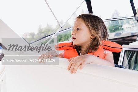 Close-up of 3 year old girl in orange life jacket on a motorboat, Sweden