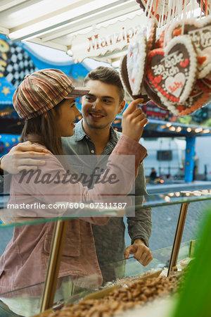 Young couple having fun at amusement park, Germany