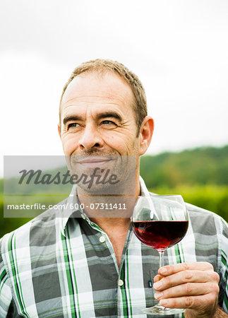 Portrait of vintner standing in vineyard, holding glass of wine, Rhineland-Palatinate, Germany