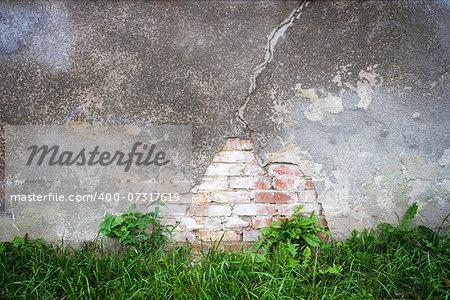 Old broken weathered wall of bricks