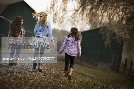 Three children walking along a path on an organic farm.