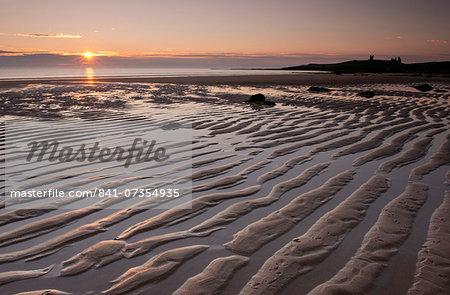 Ripples of sand near Dunstanburgh Castle in Embleton Bay at sunrise, Northumberland, England, United Kingdom, Europe