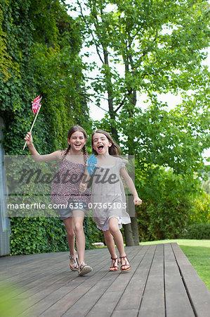 Girls running holding pinwheels