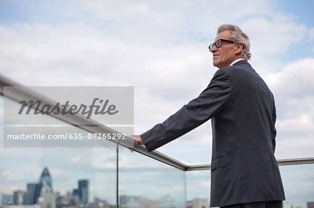 Businessman standing on balcony railing