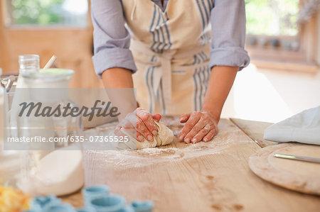 Woman kneading dough on kitchen counter