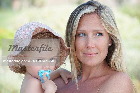 Mother hugging toddler wearing sunhat
