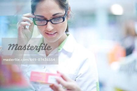 Pharmacist looking at box of medication