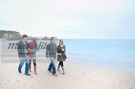 Two adult couples walking on beach, Thurlestone, Devon, UK