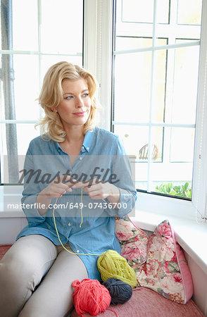 Portrait of mid adult woman knitting in window seat