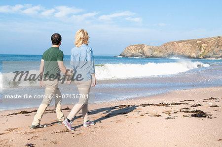 Mid adult couple walking on beach, Thurlestone, Devon, UK