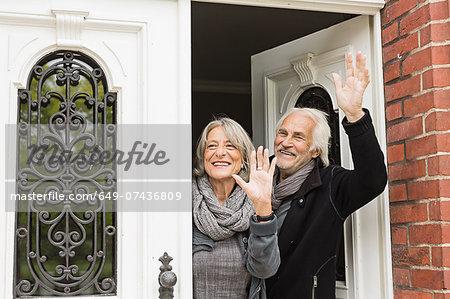 Senior couple waving by front door