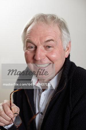 Close up portrait of senior man holding spectacles