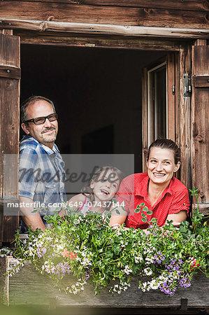 Portrait of family at chalet window, Achenkirch,  Tyrol, Austria