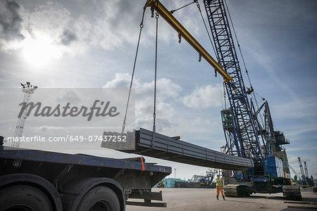 Crane unloading steel from ship in port