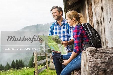 Couple with map embarking on trek, Tirol, Austria