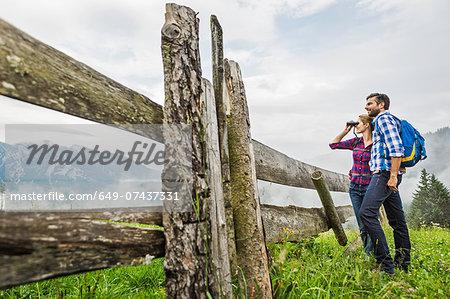 Couple enjoying view through binoculars, Tirol, Austria