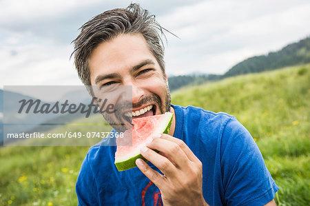 Man biting into watermelon