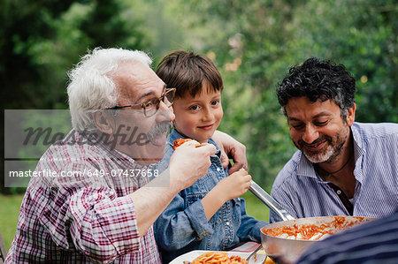 Senior man enjoying food with grandson and son