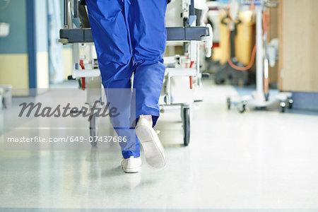 Legs of medic running with gurney along hospital corridor