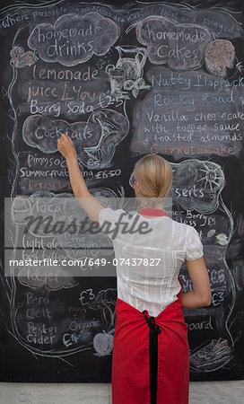 Waitress writing on blackboard menu in cafe