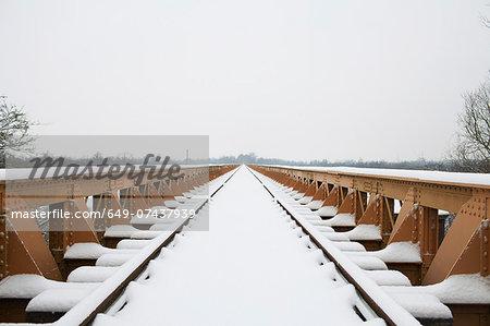 Railway track and bridge in winter snow