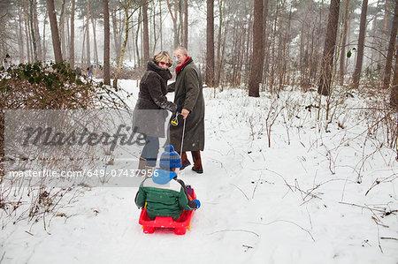 Grandparents pulling grandson on toboggan in snow