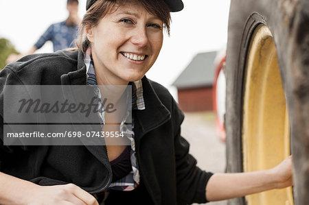 Portrait of smiling female farmer repairing tractor wheel