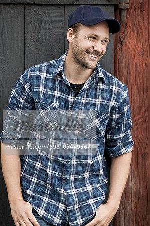Happy farmer standing with hands in pockets against barn door
