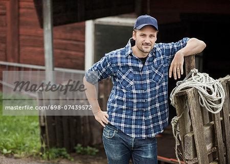 Portrait of confident farmer leaning on railing