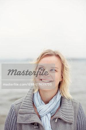 Happy woman looking away against lakeshore