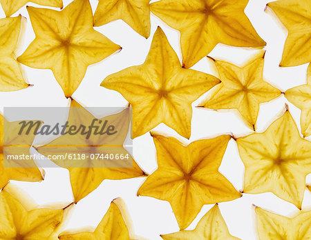 Slices of organic starfruit on a white background
