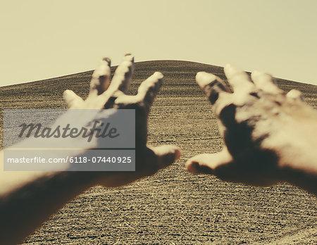 Hands extending reaching out towards ploughed farmland, near Pullman, Washington, USA