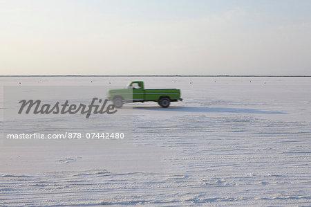 Truck driving on Bonneville Salt Flats, during Speed Week, dusk