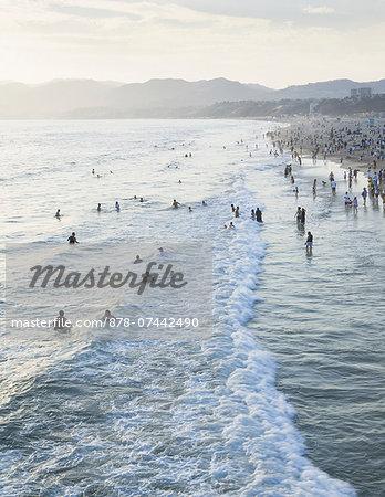 Large group of people swimming in the ocean at Santa Monica, California.
