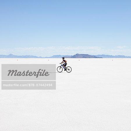 Boy riding bike on salt flats, during Speed Week