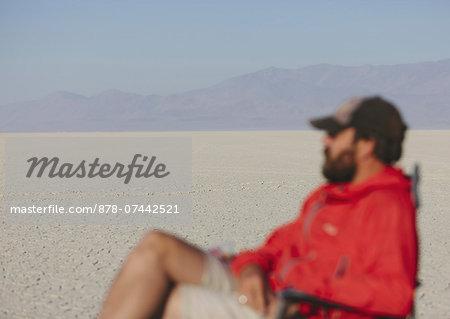 Man sitting in chair in vast, barren desert, blurred focus